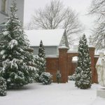 Snow on statue in winter view of Falcon Rest Mansion's gardens